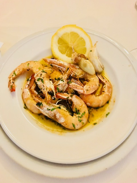 a bowl of king prawns cooked in oil and seasoned with a wedge of lemon