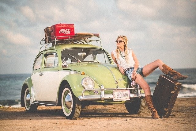 lady leaning on the bonnet of a volkswagon bettle car