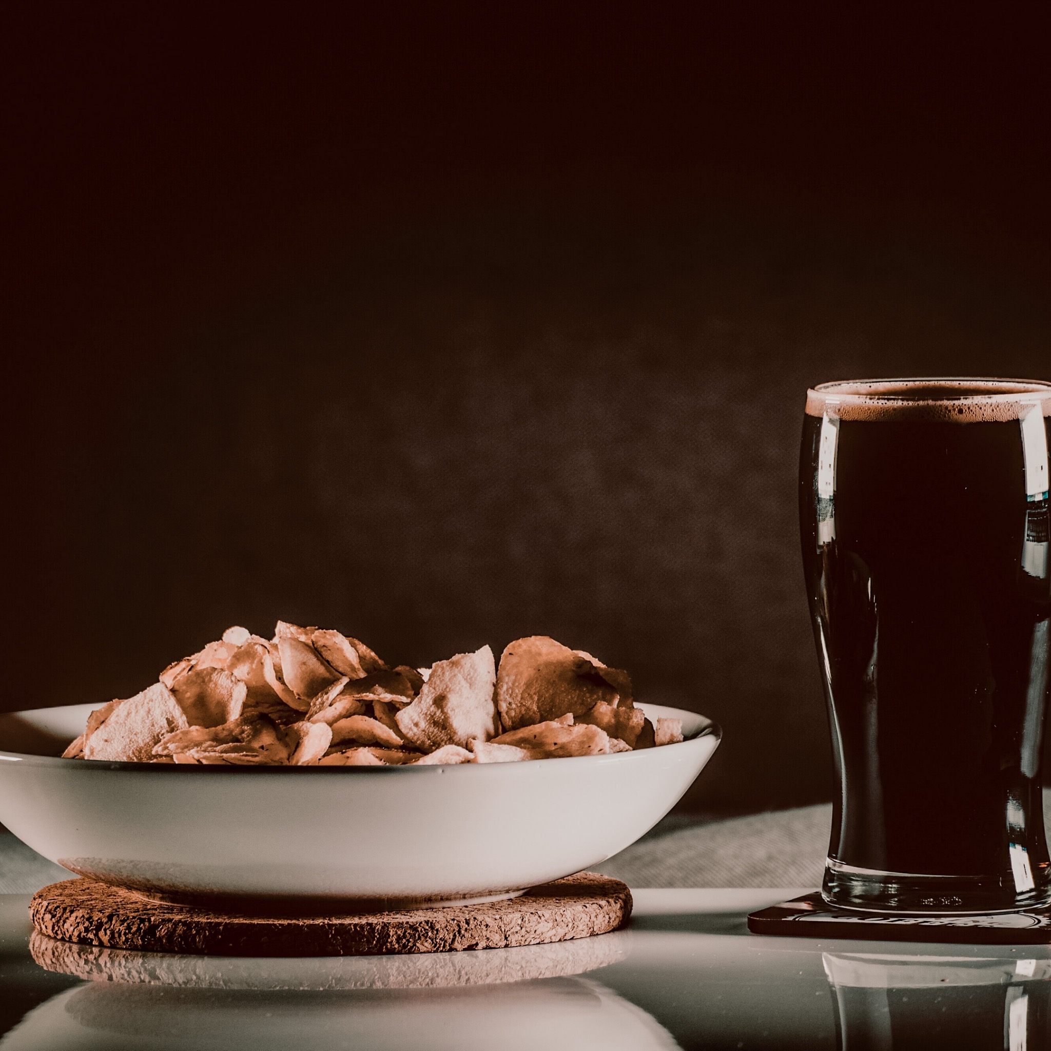 crisps in a bowl and a pint glass of beer