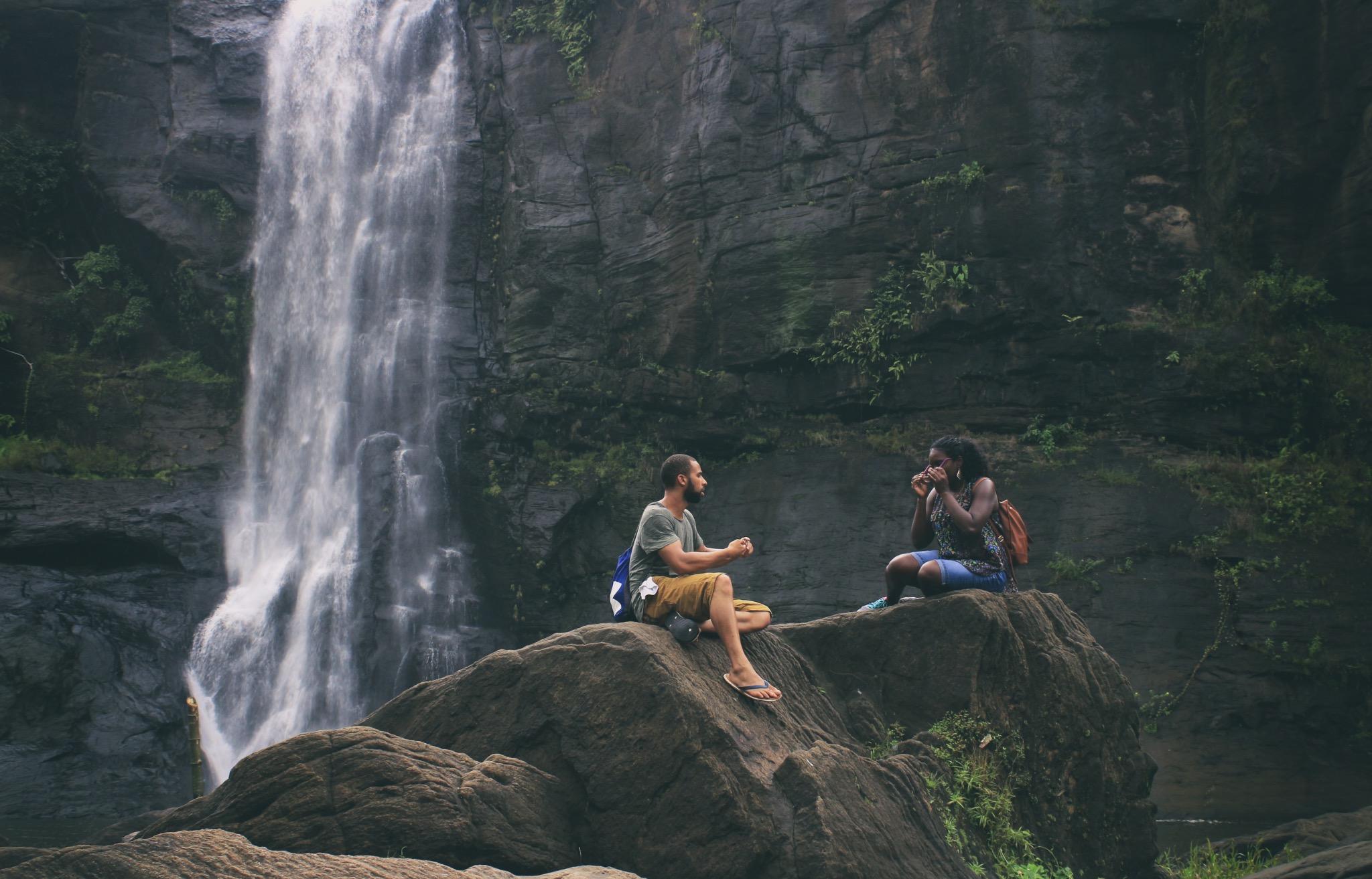 man and woman near waterfall