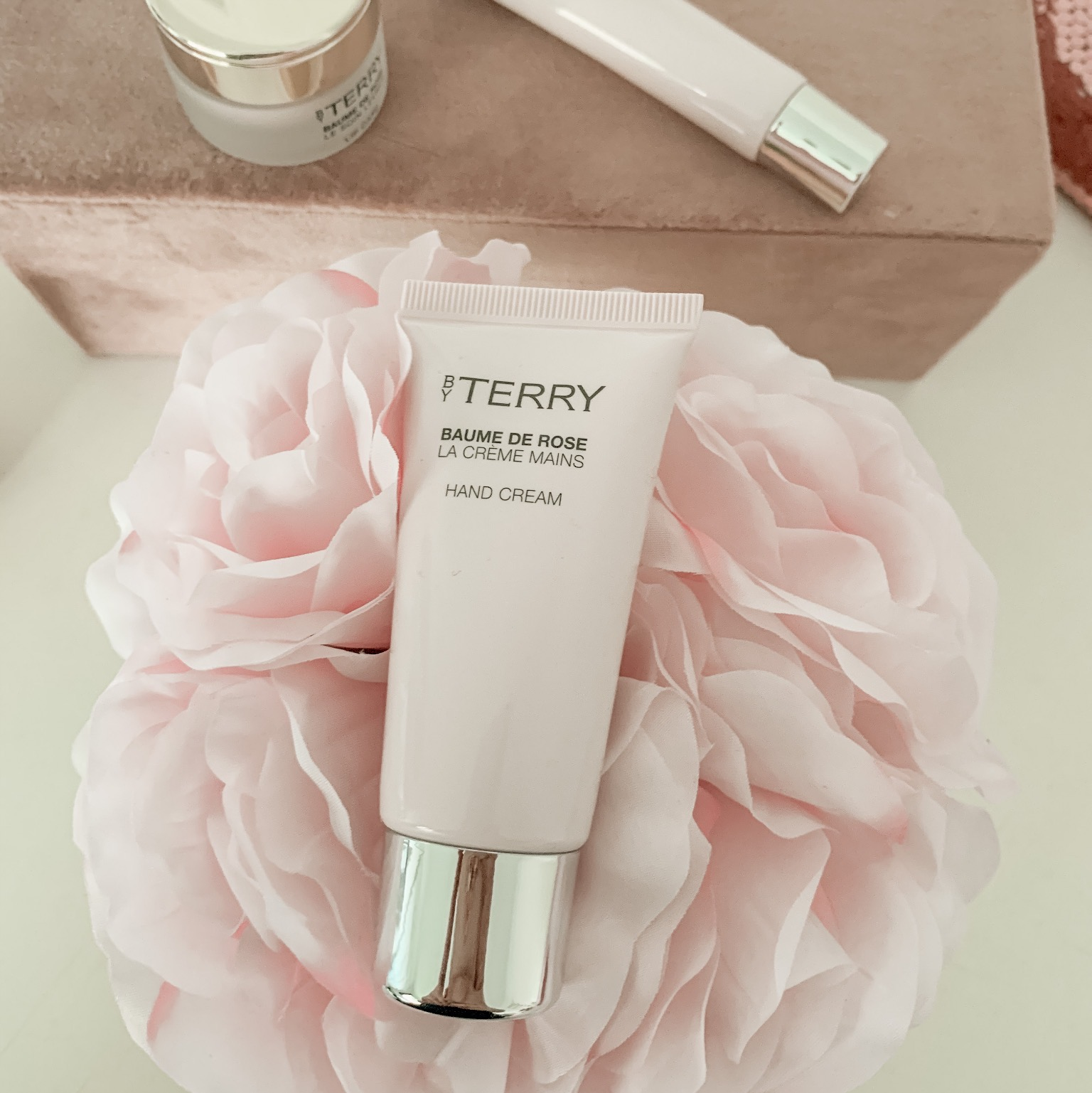 a pale pink tube of hand cream sitting on top of a pale pink bunch of flowers