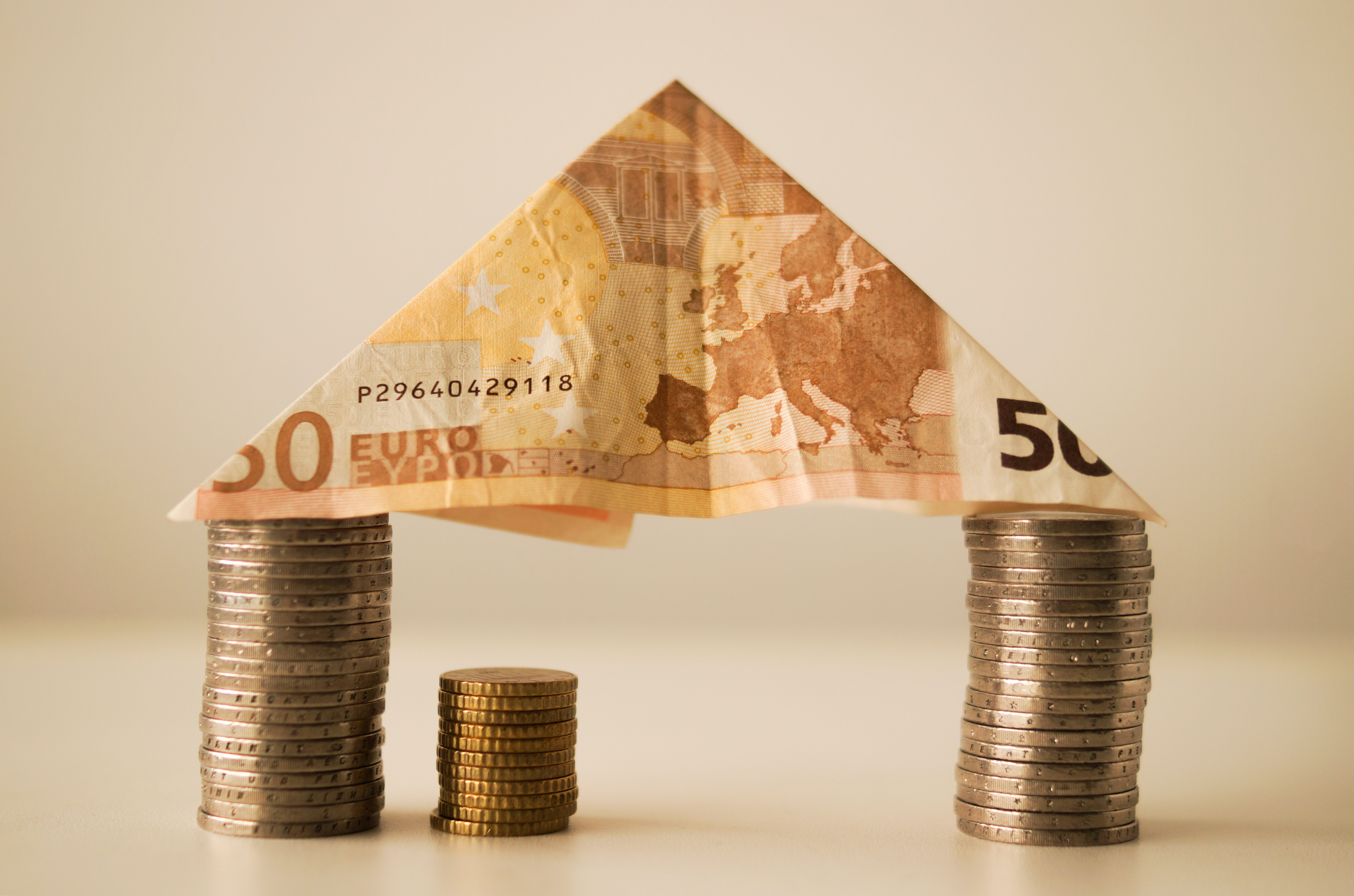 a euro note on top of a stack of euro coins making a house shape