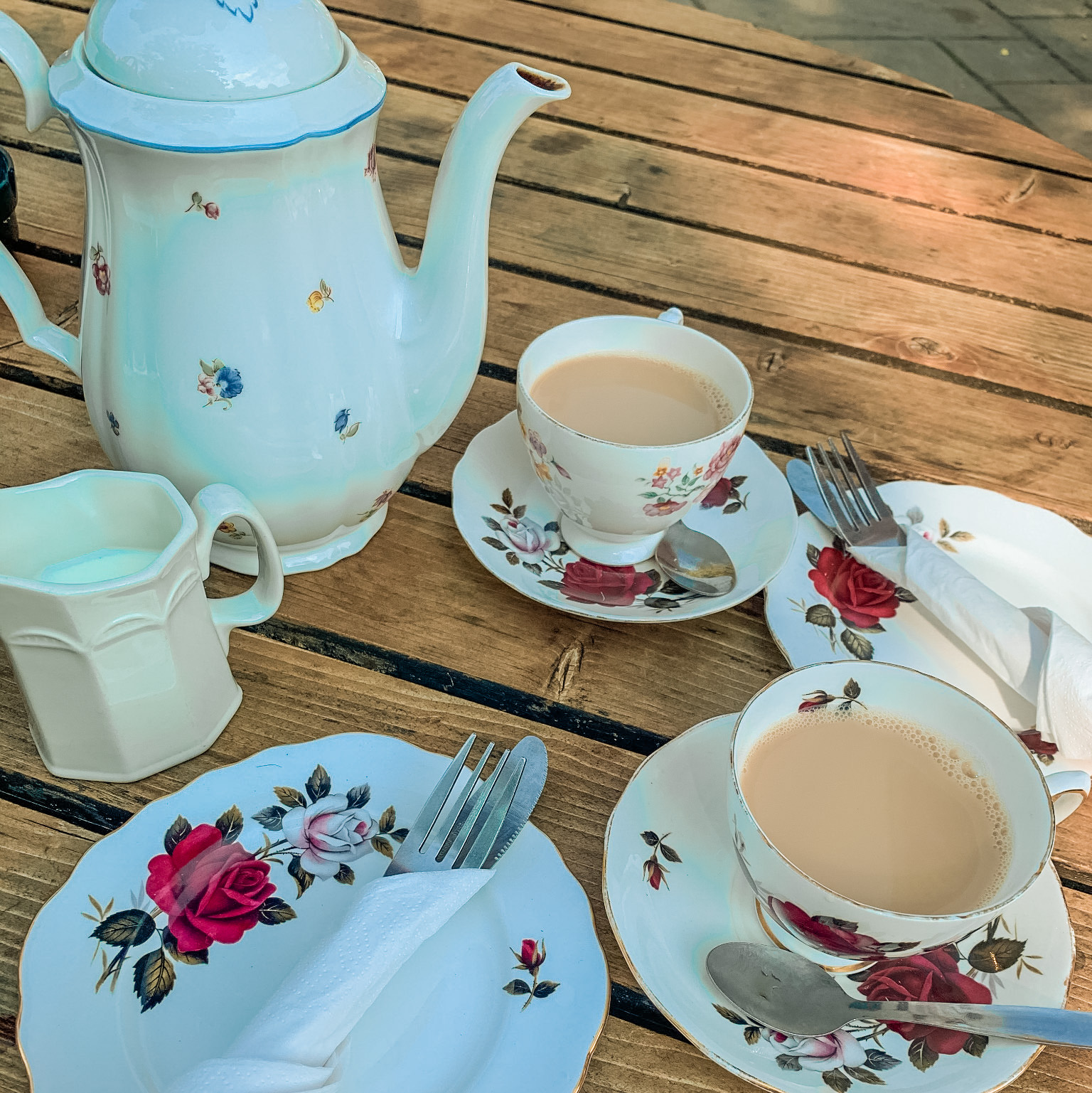 a floral tea set consisting of a teapot, milk jug and 2 cups with saucers