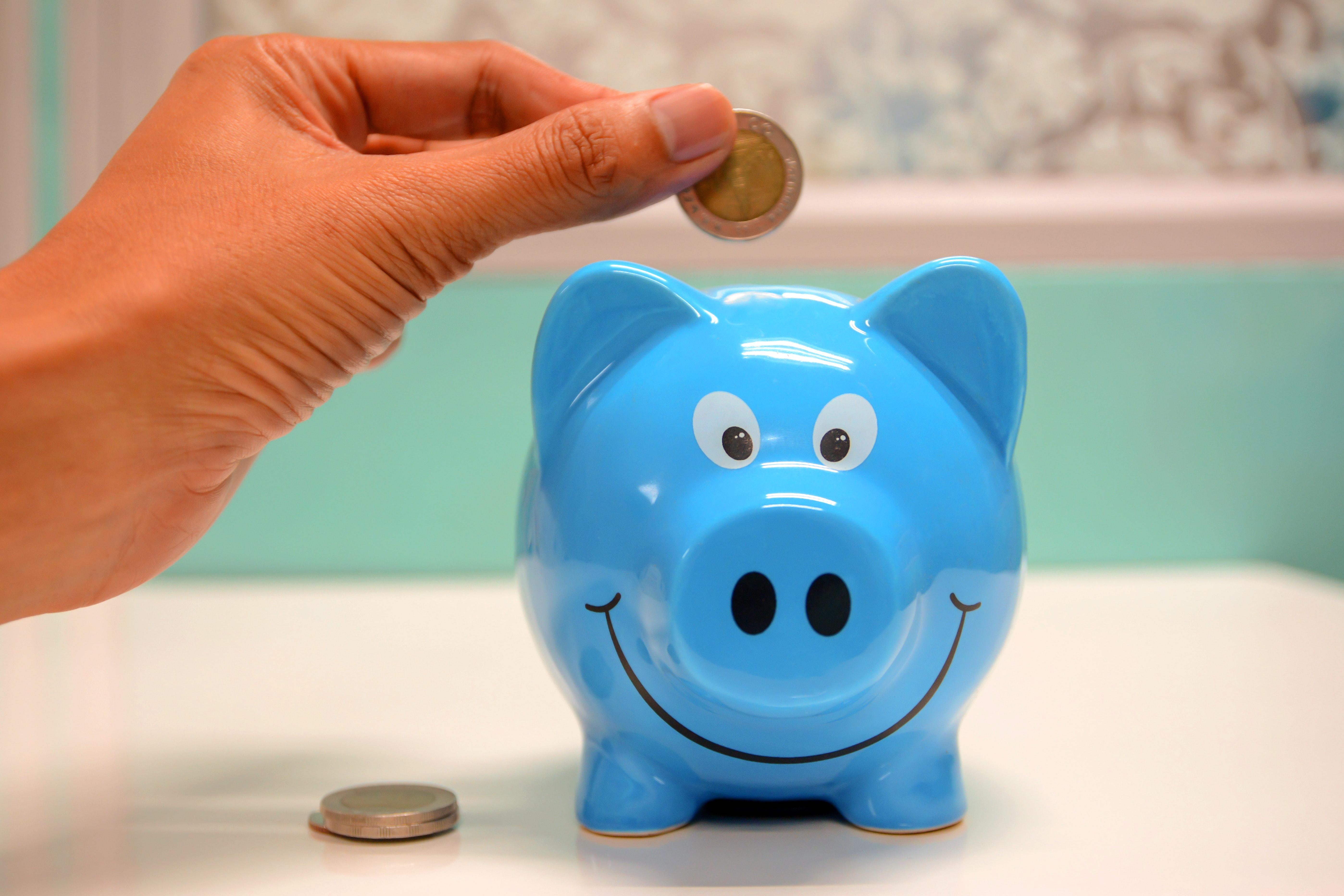 person holding a coin over a piggy bank