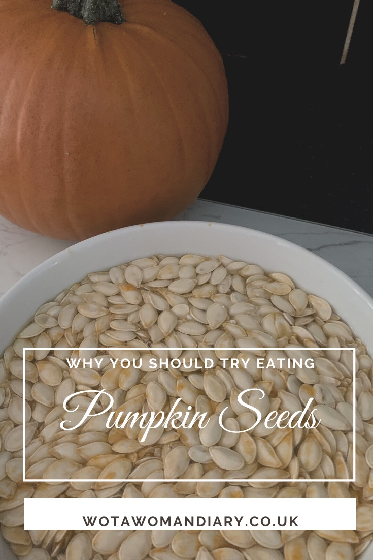 a close up of a bowl of pumpkin seeds with a pumpkin in the back ground
