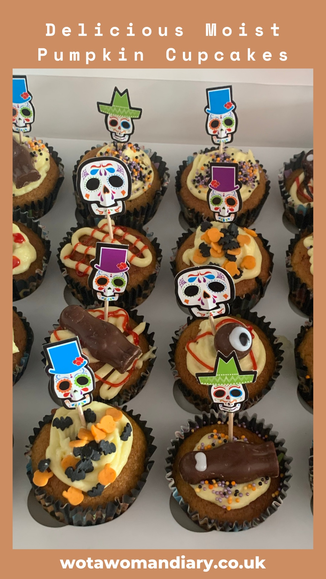 a tray of decorated pumpkin cupcakes looking delicious