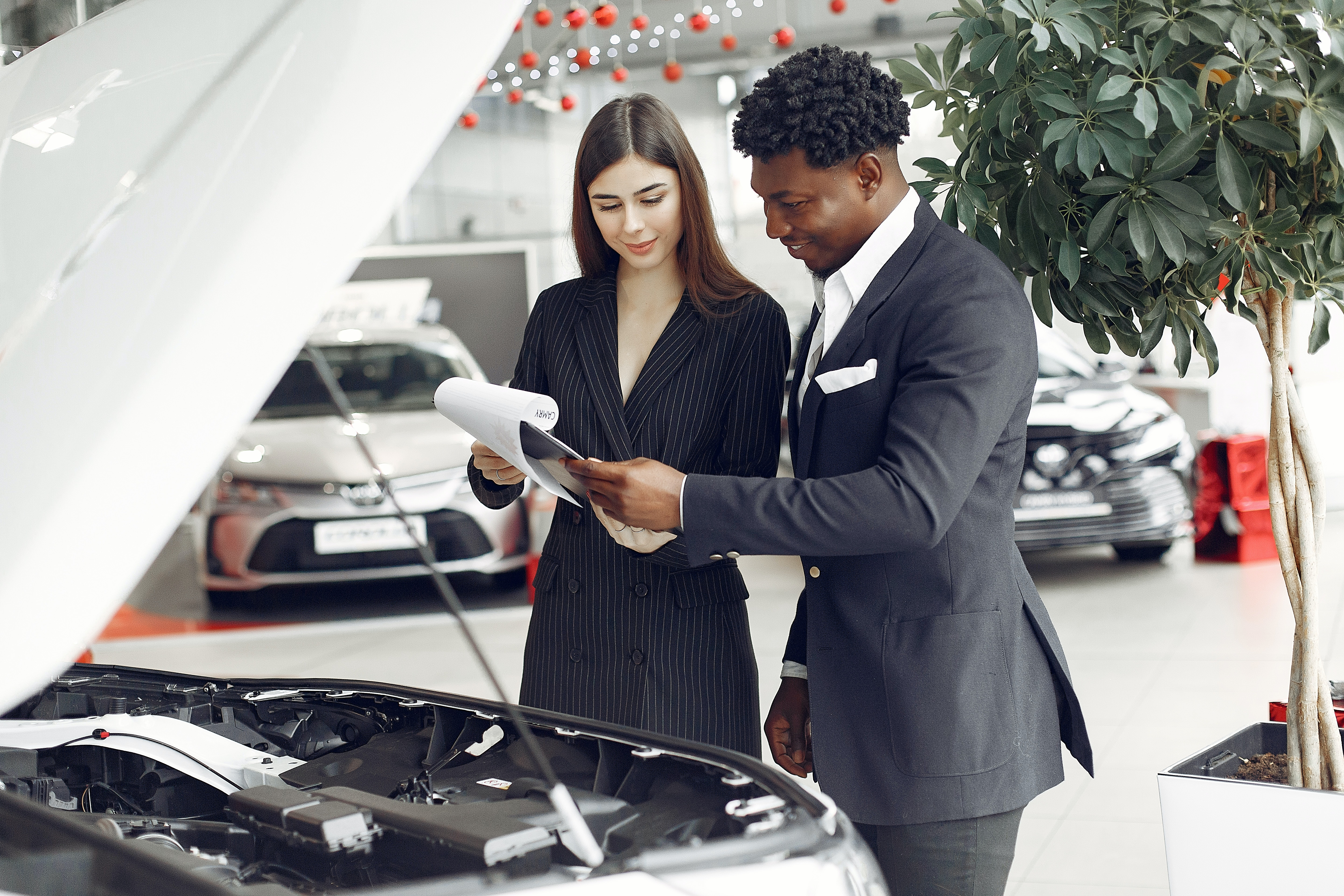2 people discussing final checks standing in front of a car with the bonnet open